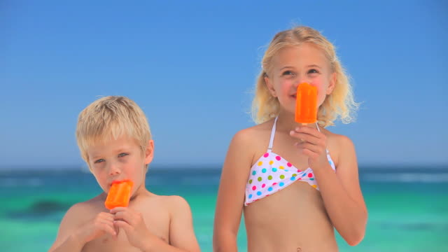 Blond children eating water ices on the beach / Cape Town, Western Cape, South Africa
