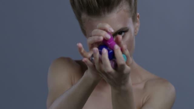 vídeos de stock, filmes e b-roll de loira modelo lida com 4 frascos de esmalte. vídeo de moda. - maquiagem para teatro