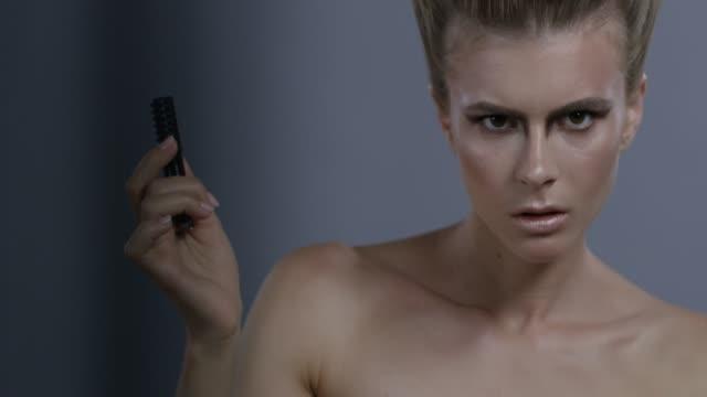 Blond fashion model handles black eyeliner. Fashion video.