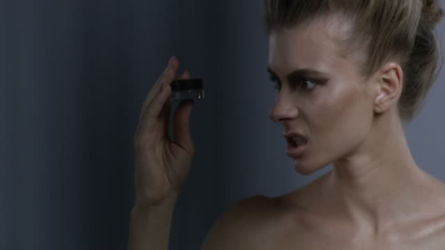 blond fashion model in stage make-up handles blue eyeshadow jar, hissing on it. fashion video. - lip liner stock videos & royalty-free footage