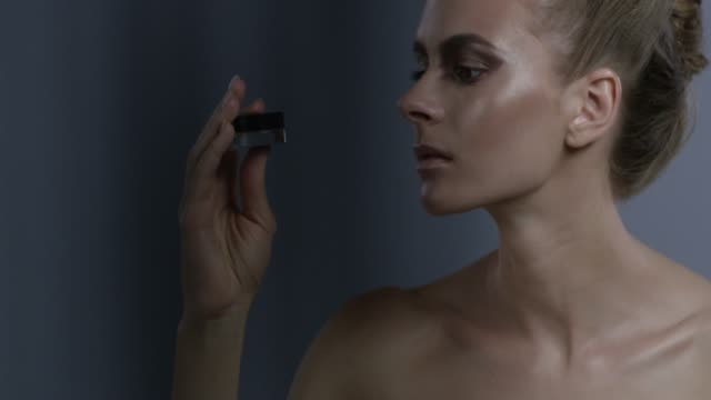 blond fashion model in stage make-up handles blue eyeshadow jar. fashion video. - greasepaint stock videos and b-roll footage