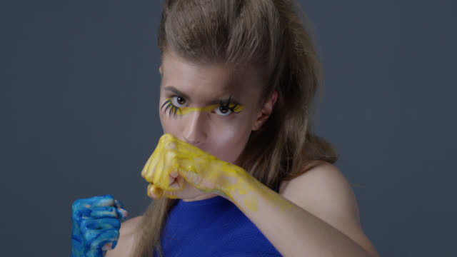 vidéos et rushes de mannequin blonde dans le maquillage de scène (ombres à paupières jaune et rouge à lèvres bleu) avec les faux cils se bat, ses mains sont peinte bleu et jaune, symbolisant le drapeau ukrainien. mode vidéo. - force