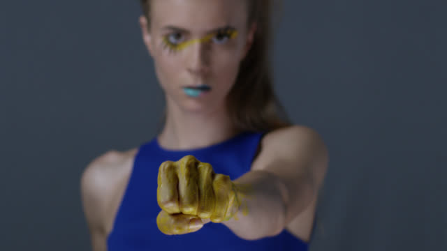 Blond fashion model in stage make-up (yellow eyeshadows and blue lipstick) with faux lashes is fighting , her hands are painted blue and yellow, symbolizing Ukrainian flag. Fashion Video.