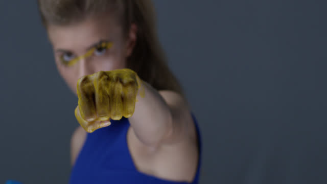 blond fashion model in stage make-up (yellow eyeshadows and blue lipstick) with faux lashes is fighting , her hands are painted blue and yellow, symbolizing ukrainian flag. fashion video. - fighter stock videos & royalty-free footage