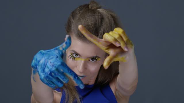金髪ファッションモデル偽まつげと舞台メイク (黄色のアイシャドウと青い口紅) に描かれた青と黄色、ウクライナの旗を象徴する彼女の手に移動します。ファッションのビデオ。 - アイシャドウ点の映像素材/bロール