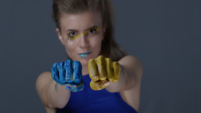 blond fashion model in stage make-up (yellow eyeshadows and blue lipstick) with faux lashes moves her hands, painted blue and yellow, symbolizing ukrainian flag. fashion video. - greasepaint stock videos and b-roll footage