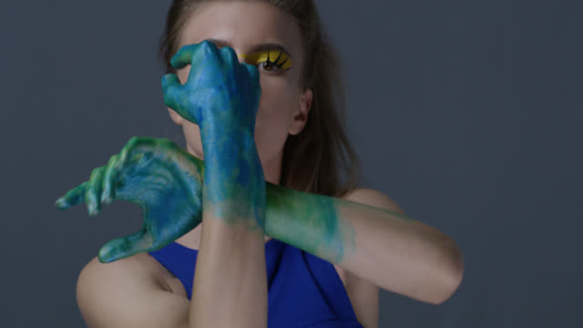 blond fashion model in stage make-up (yellow eyeshadows and blue lipstick) with faux lashes moves her hands, painted green. fashion video. - modern dancing stock videos & royalty-free footage