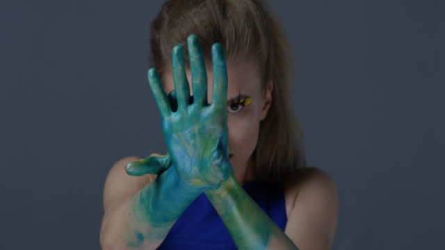 Blond fashion model in stage make-up (yellow eyeshadows and blue lipstick) with faux lashes moves her hands, painted green. Fashion Video.