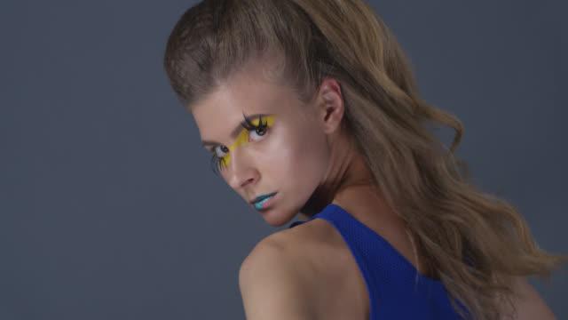 vídeos de stock, filmes e b-roll de modelo loira na maquiagem de palco (amarelas sombras e batom azul) com chicotadas do falso vira e mostra expressões faciais. vídeo de moda. - maquiagem para teatro
