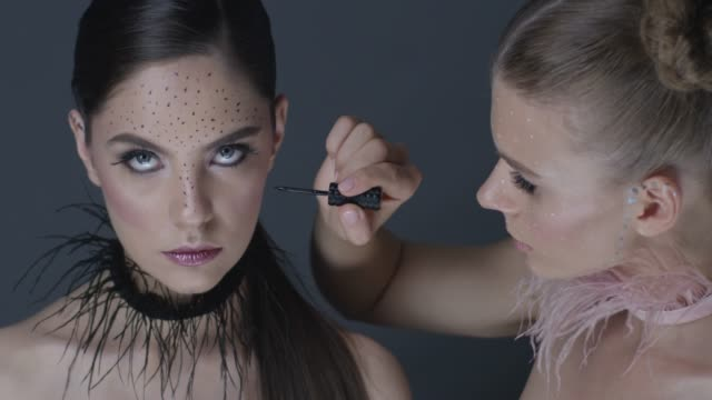 Blond fashion model paints freckles on brunette model`s face with eyeliner. Fashion Video.