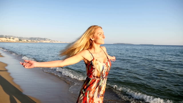 Blond girl carefree at the beach