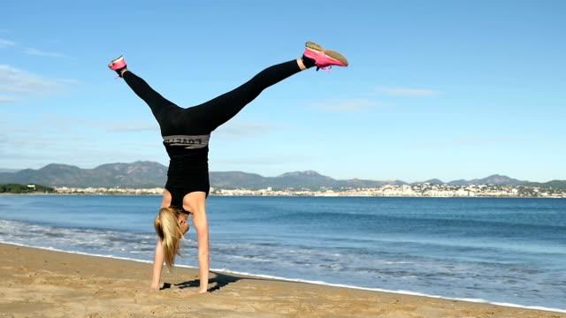 Blond girl doing a cartwheel on the beach