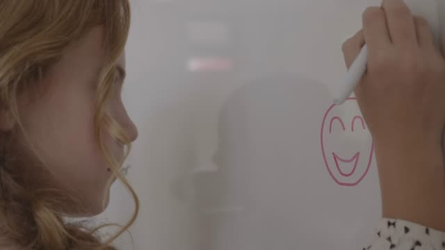 blond girl drawing with friend on whiteboard - school supplies stock videos & royalty-free footage