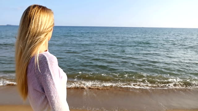 Blond girl looking at sea view