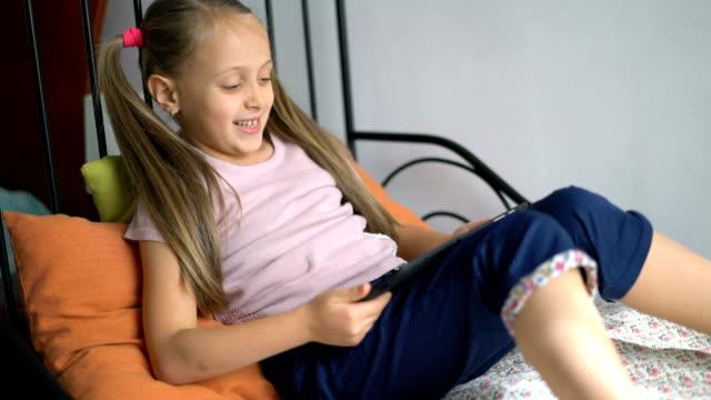 Blonde Mädchen mit den digitalen Tablet zu Hause spielen.