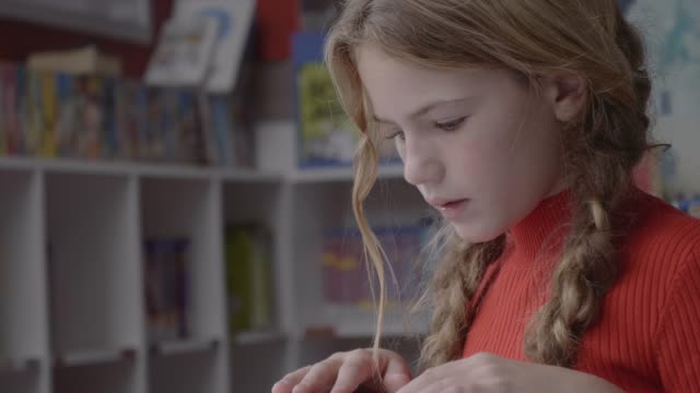 vídeos de stock e filmes b-roll de blond girl reading picture book at desk - ler