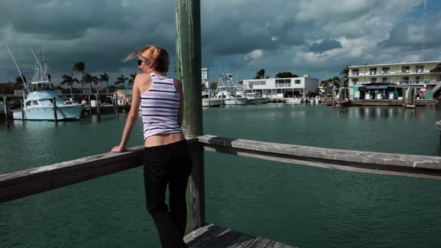 Blond girl relaxing in a marina,looking at boats