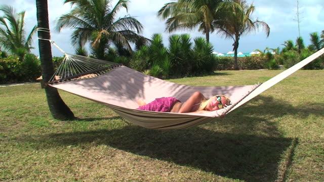 vidéos et rushes de blonde fille dormir sur un hamac - jardin classique