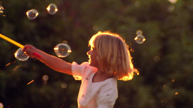 vidéos et rushes de ms blond girl spinning with bubble making toy + bubbles outdoors - children only