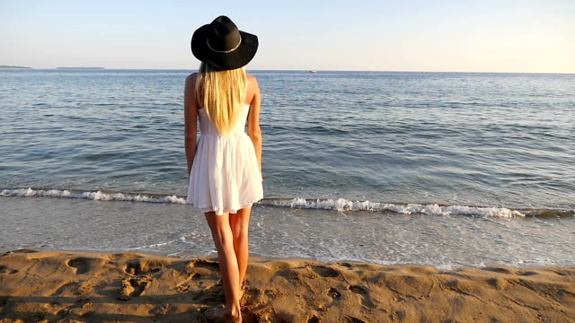 Blond girl standing at the edge of the sea