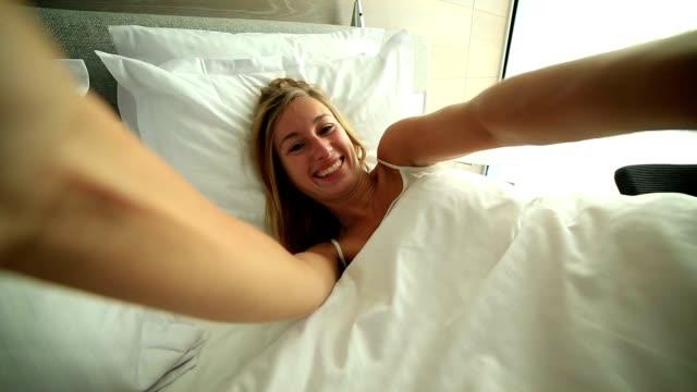 Blond girl takes selfie in bed