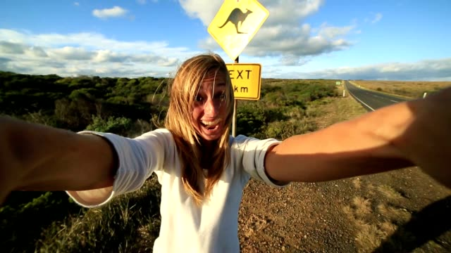 blond girl traveling takes selfie with kangaroo crossing sign - road warning sign stock videos & royalty-free footage