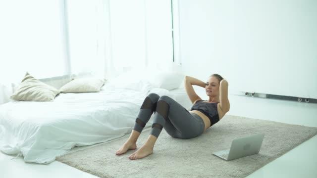 blonde haare, frau trainiert zu hause mit dem computer - abnehmen stock-videos und b-roll-filmmaterial