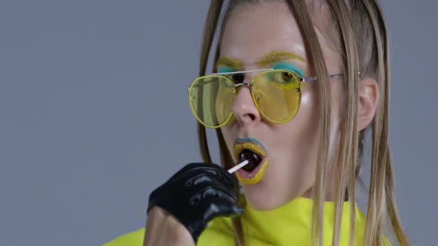 Blonde High-Fashion-Modell in hellen Bühne Make-up, tragen gelbe Sonnenbrillen und schwarze Lederhandschuhe, leckt Lutscher. Close-up. Mode-Video.