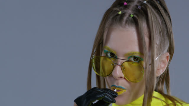 blond high fashion model in bright stage make-up, wearing yellow sunglasses and black leather gloves, licks lollipop. close-up. fashion video. - stage make up stock videos and b-roll footage