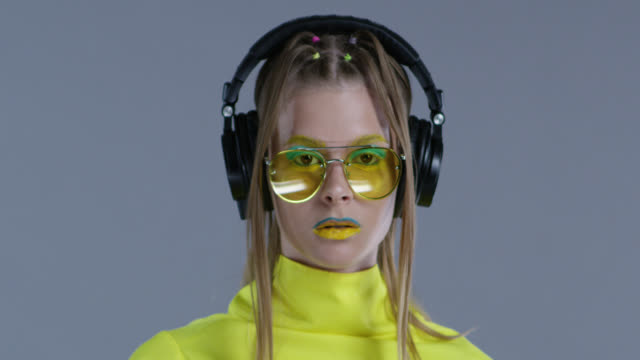blond high fashion model in bright stage make-up, wearing yellow sunglasses and black leather gloves, listens to music in big wireless headphones. statics. close-up. fashion video. - listening stock videos & royalty-free footage