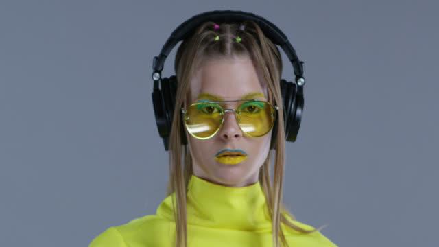Blonde High-Fashion-Modell in hellen Bühne Make-up, tragen gelbe Sonnenbrillen und schwarze Lederhandschuhe, hört Musik im großen Funkkopfhörer. Statik. Close-up. Mode-Video.