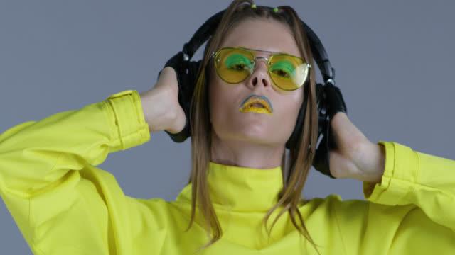 Blonde High-Fashion-Modell in hellen Bühne Make-up, tragen gelbe Sonnenbrillen und schwarze Lederhandschuhe, hört Musik im großen Funkkopfhörer. Close-up. Mode-Video.