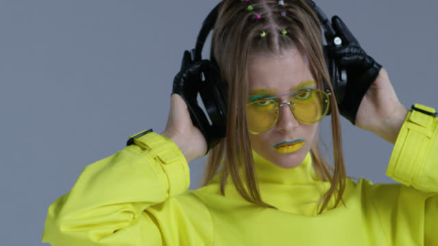 blond high fashion model in bright stage make-up, wearing yellow sunglasses and black leather gloves, listens to music in big wireless headphones. close-up. fashion video. - sunglasses stock videos & royalty-free footage