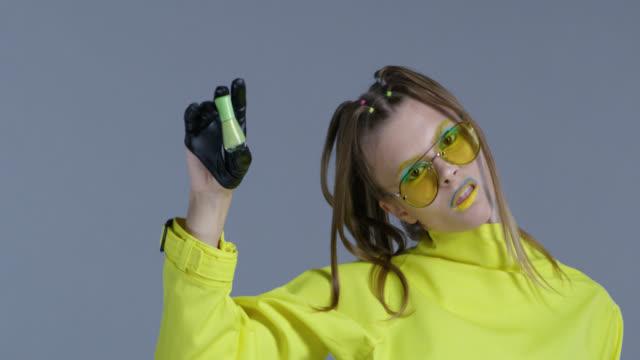vídeos y material grabado en eventos de stock de modelo rubia alta moda en maquillaje de la etapa brillante, usar gafas de sol amarillo y guantes de cuero negro, muestra el esmalte de uñas verde botella. close-up. video de la moda. - sombreador de ojos