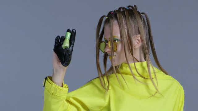 vídeos de stock, filmes e b-roll de modelo loira alta moda em maquiagem de palco brilhante, usando óculos de sol amarelos e luvas de couro preto, mostra esmalte verde garrafa. close-up. vídeo de moda. - boca humana