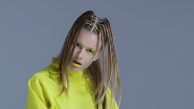vídeos y material grabado en eventos de stock de rubia alta moda modelo en etapa brillante maquillaje amarillo y azul se mueve. video de la moda. - sombreador de ojos