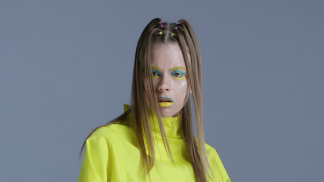 blond high fashion model in bright stage make-up yellow and blue moves. fashion video. - modella video stock e b–roll