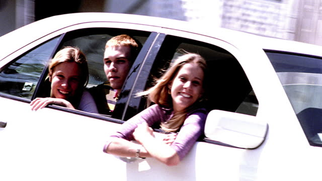 overexposed canted ms pan blond teen boy + two blond teen girls leaning out of passing car windows - overexposed video stock e b–roll