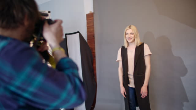 Blond transgender person posing against backdrop during photo shoot