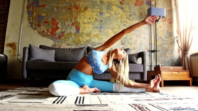 blond kvinna gör yoga hemma i vardagsrummet - idrotta bildbanksvideor och videomaterial från bakom kulisserna