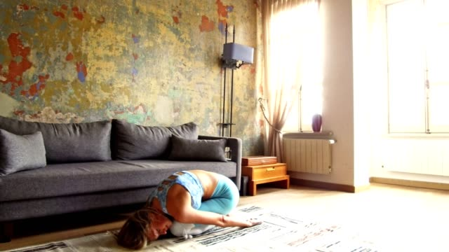 blond woman doing yoga at home in the living room - good posture stock videos & royalty-free footage