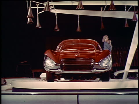 1956 blond woman holding dog posing next to futuristic buick concept car on spinning platform - collector's car stock videos and b-roll footage