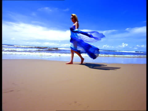 a blond woman in a flowing blue dress walks near the surf on a beach. - dress stock videos & royalty-free footage