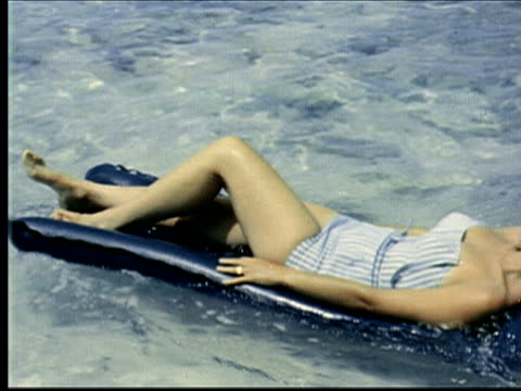 stockvideo's en b-roll-footage met montage blond woman in bikini lying face up on raft floats by man lying face down on raft. blond woman glides around on raft. black dog wearing sunglasses floats by on raft / bermuda - 1963