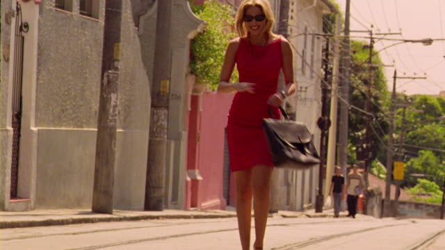 Blond woman in red dress with briefcase excitedly walking on city street + spinning
