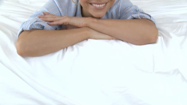 blond woman lying on bed - hand am kinn stock-videos und b-roll-filmmaterial