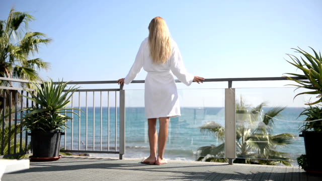 blond woman on a balcony with sea view - balcony stock videos & royalty-free footage