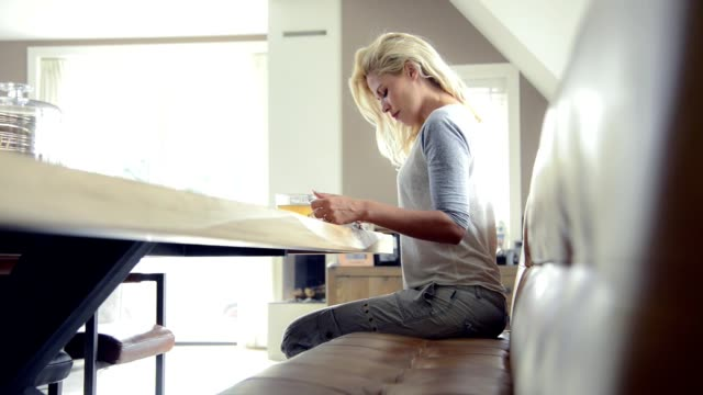 Blond woman relaxing, reading and morning tea