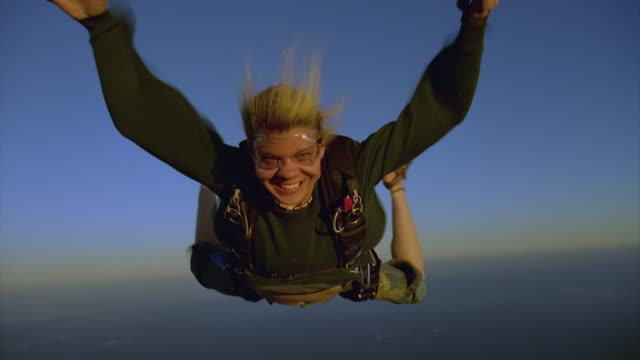Blond woman skydiving in street clothes