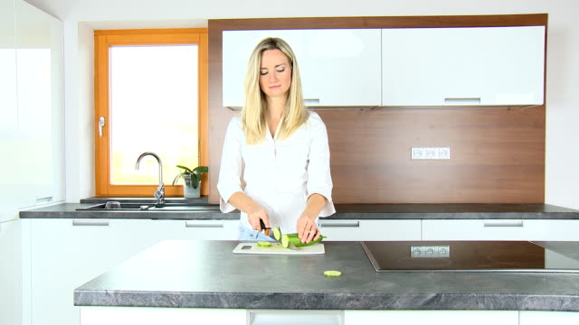 blond woman slicing cucumber - white shirt stock videos & royalty-free footage